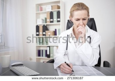 stock-photo-serious-adult-female-medical-doctor-reading-medical-documents-on-the-table-with-one-hand-on-her-271306187